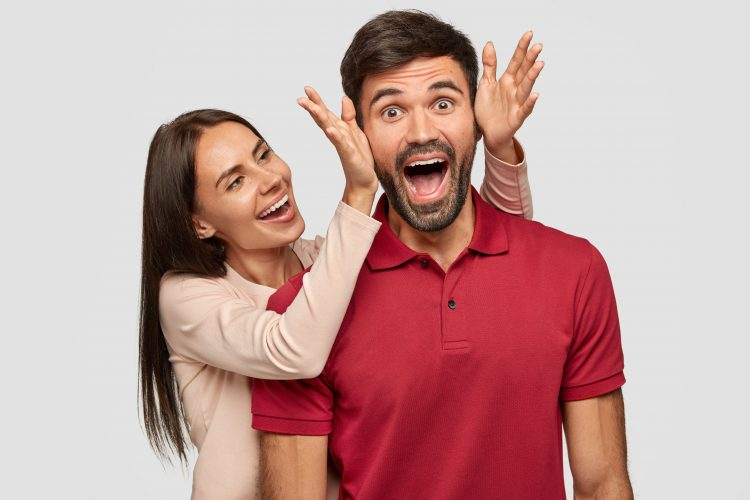 People, joy, pleasant moment in life. Overjoyed brunette European young female stands near her boyfriend, going to cover eyes and make surprise, have fun together, isolated over white background.